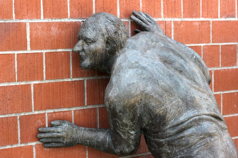 Sculpture of man listening to wall