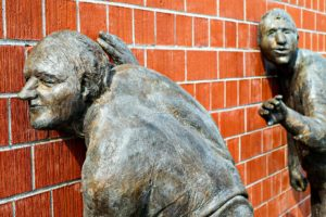 Two bronze sculptures of men listening to a wall