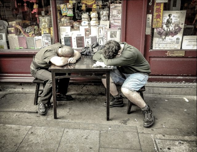Two workers resting at a table with heads down.